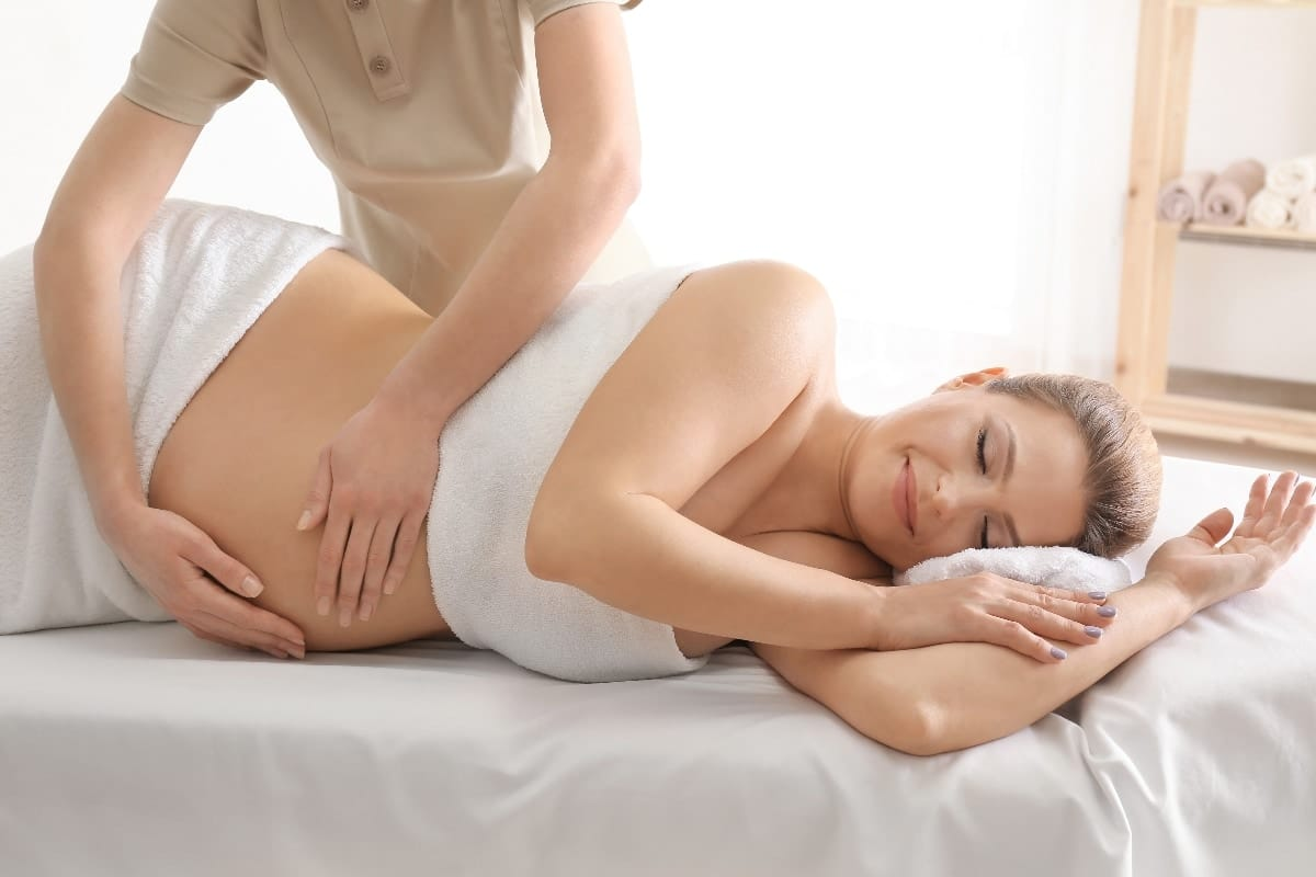 Young beautiful pregnant woman having massage in spa salon